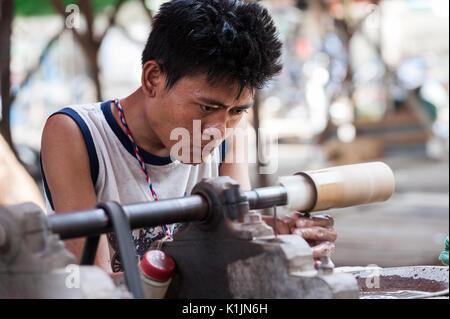 Man polishes gemstones in Jade Market, Mandalay, Myanmar. - Stock Photo