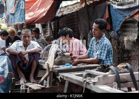 Jade market workers at their workshops, Mandalay, Myanmar. - Stock Photo