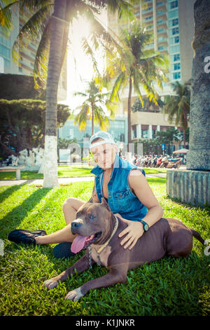 Man and dog american pit bull terrier relaxing at the park embracing and hugging