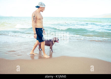 Young man with dog american pit bull terrier walking on the tropical beach - Stock Photo