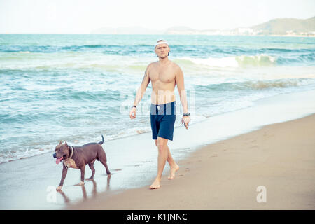 Young man with dog american pit bull terrier walking on seashore - Stock Photo