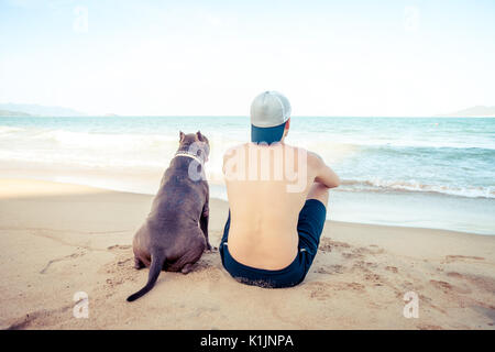 Friendship concept, man and dog sitting together on the beach at sunset - Stock Photo