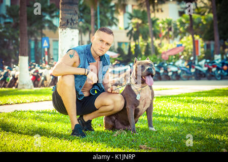 Happy friends man and dog american pit bull terrier sitting on grass in park - Stock Photo