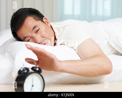 asian man lying in bed trying to stop ringing alarm clock. - Stock Photo