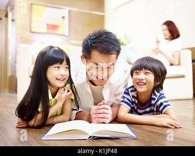 asian father and children lying on floor reading book with mother in the background. - Stock Photo