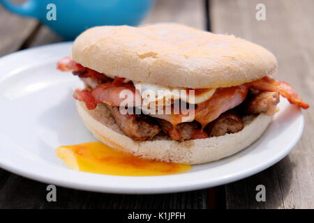 A freshly cooked breakfast bap. Bacon, sausage and fried egg cooked at a outdoor cafe and served in a bread roll. - Stock Photo