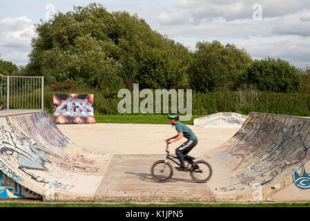 A teenager on a bmx riding on a concrete half pipe ramp at Stratford on Avon skate park during the summer holidays. - Stock Photo