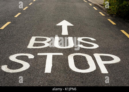 Bus Stop Sign and ahead Arrow painted in white on an asphalt road with yellow markings. - Stock Photo