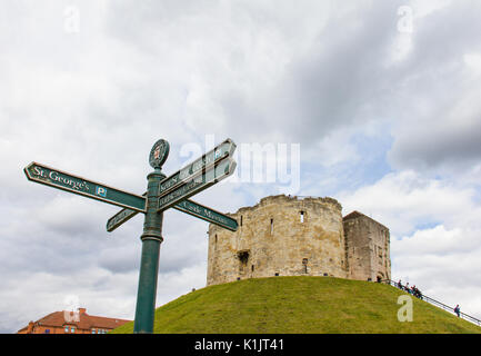 York, United Kingdom - 6 August, 2017: Clifford's Tower at York city center on a green grass hill and pedestrian - Stock Photo