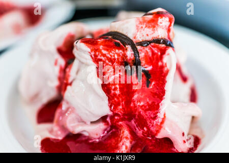 Soft serve vanilla ice cream with red strawberry sauce and drizzled chocolate syrup closeup in bowl - Stock Photo