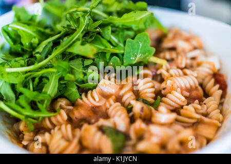 Closeup of brown rice fusilli pasta bowl in marinara sauce with arugula greens - Stock Photo