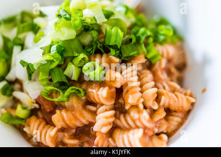 Closeup of brown rice fusilli pasta bowl in marinara sauce topped with green onions - Stock Photo
