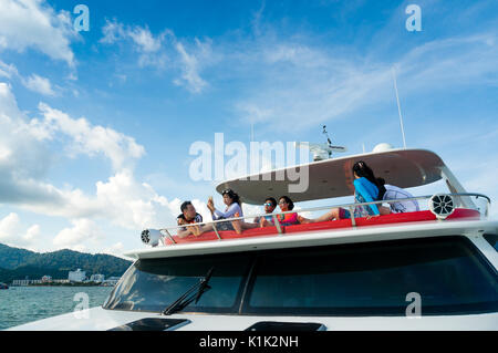 Langkawi, Malaysia - 3rd May 2017: Rich young people crusing on a yacht on sunny day with blue sky and whispy clouds. - Stock Photo
