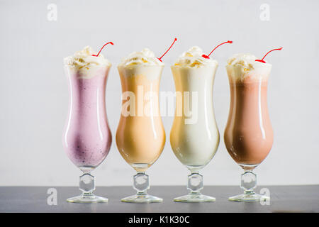 Row of various sweet milkshakes with cherries in glasses on the table - Stock Photo