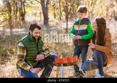 Portrait of happy family with one child preparing barbecue on grill in autumn park