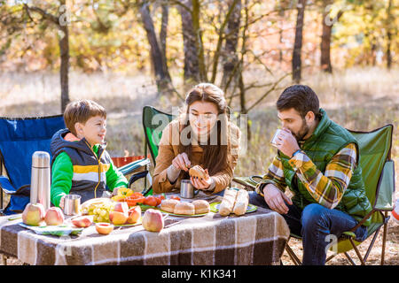 Happy smiling family eating and having fun while sitting at table on picnic in autumn forest - Stock Photo