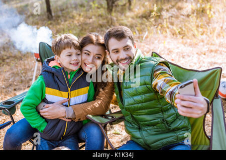 Happy smiling family at picnic having fun and taking selfie in autumn park - Stock Photo