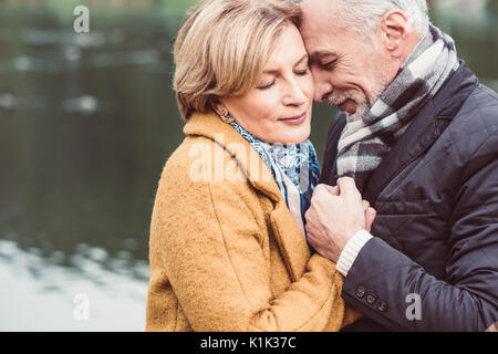 Close-up portrait of beautiful mature couple standing and holding hands near lake in autumn park - Stock Photo