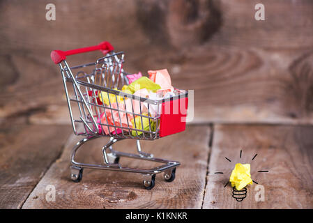 Shopping cart and small paper balls. Recylcing concept with color paper and shopping cart - Stock Photo