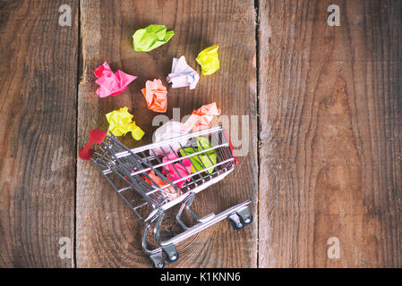 Shopping cart and small paper balls. Thinking about new idea. Ideas about e-commerce, e-commerce or commerce - Stock Photo