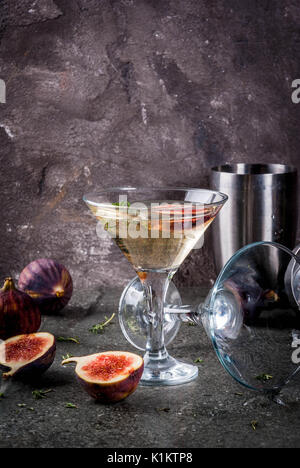 Fall and winter drinks recipes, Martini cocktail with fig, thyme and honey, on black stone table, copy space - Stock Photo