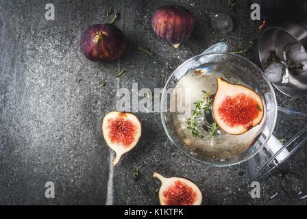 Fall and winter drinks recipes, Martini cocktail with fig, thyme and honey, on black stone table, copy space top - Stock Photo
