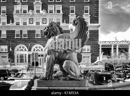 A winged lion statue from the Grove Arcade in profile, with the Battery Park Hotel in the background, in Asheville, - Stock Photo