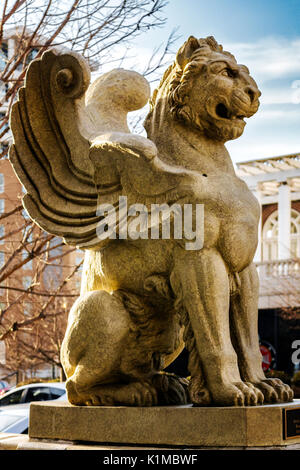 A statue of a winged lion with tree limbs and the Batter Park Hotel in the background in Asheville, North Carolina - Stock Photo