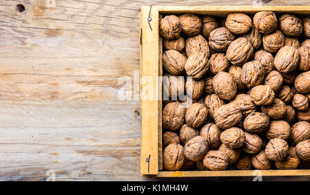 Box of walnuts on wooden background. Harvest concept - Stock Photo