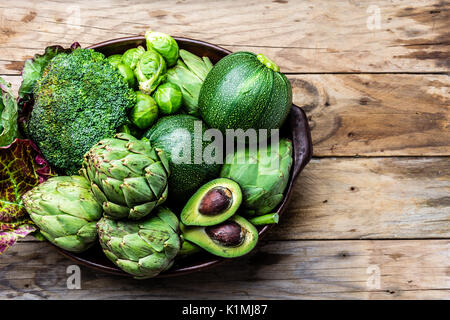 Cooking background harvest concept. Fresh organic green vegetables in clay pot on wooden background - Stock Photo