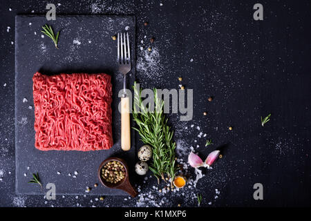 Raw fresh lamb meat and meat fork on dark background, burger patty ingredients. Top view. Free space. - Stock Photo