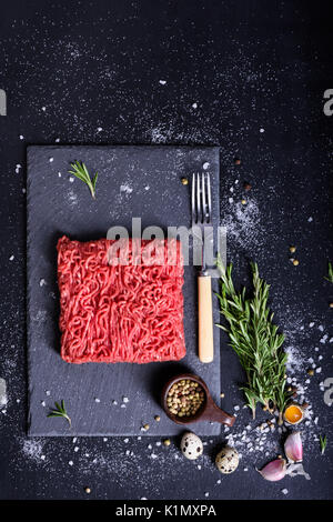 Raw marbled ground meat steak with rosemary, pepper and salt on stone slate background. Top view, copy space. - Stock Photo