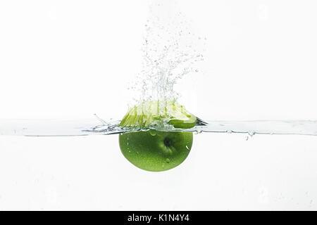 Green apple thrown in water shot - Stock Photo