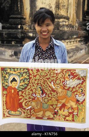 Woman with thanaka on face selling artwork at temple in Pagan (Bagan), Burma (Myanmar) - Stock Photo
