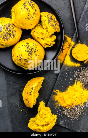 Bread burger buns with superfoods curcuma and chia on slate blackbackground. Top view - Stock Photo