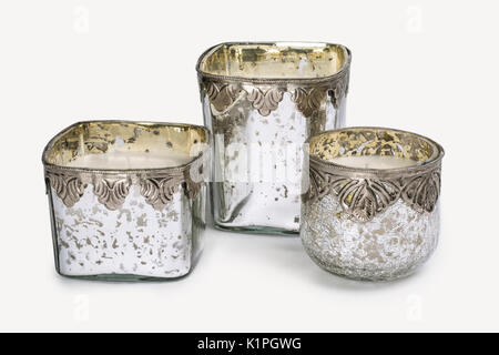 CLOSE UP IMAGE OF THREE ROUND RUSTIC SILVER AND GOLD CRACKLED GLASS CANDLEHOLDERS AND CANDLES ISOLATED ON WHITE - Stock Photo