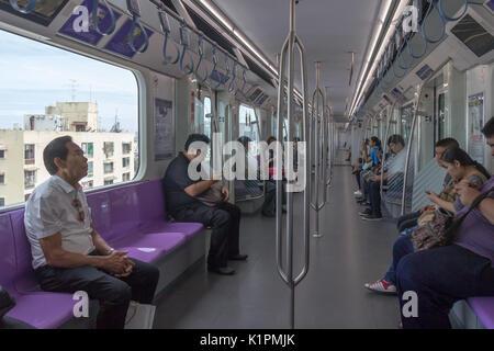 Passengers seated on the purple line  MRT train, Bangkok, Thailand - Stock Photo