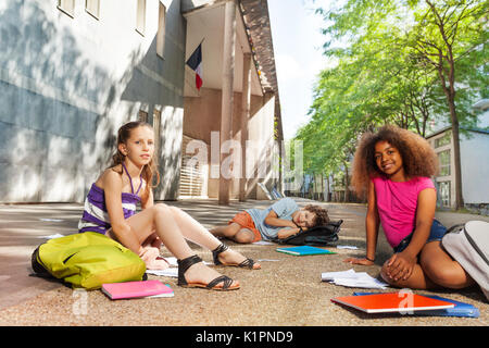 Group of kids sit on the ground with textbooks and books near school - Stock Photo