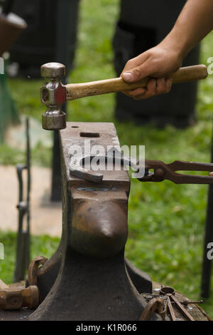 Farrier producing horseshoes in the traditional method on an anvil. - Stock Photo