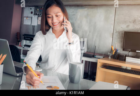 Asian businesswoman with smiling face talking on mobile and writing analyze business data on sheet on desk with - Stock Photo