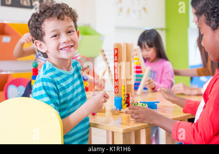Kindergarten students smile when playing toy in playroom at preschool international,education concept. - Stock Photo
