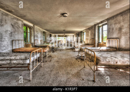 Dilapidated dormitory in an abandoned children hospital - Stock Photo