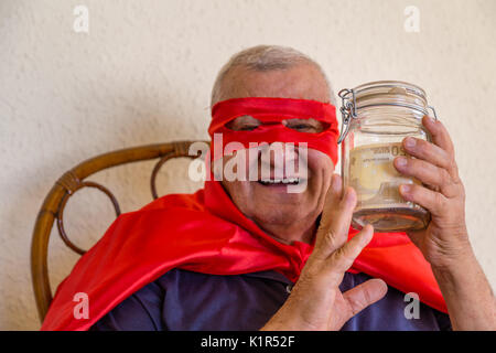 old man dressed as super hero smiling while sitting on wicker chair and  holding a jar full of euro banknotes on - Stock Photo