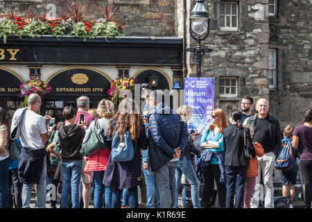 Tourists crowding around and photographing Greyfriars Bobby, famous 19th century Edinburgh SkyeTerrier Dog, on George - Stock Photo