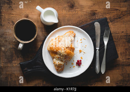 Almond croissant, silverware, cup of black coffee espresso and cream on wooden cutting board. Table top view - Stock Photo