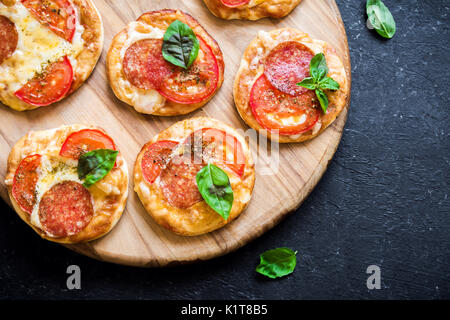 Mini Pizza - Fresh homemade mini pizzas with pepperoni, cheese, tomatoes and basil on rustic black stone background. - Stock Photo