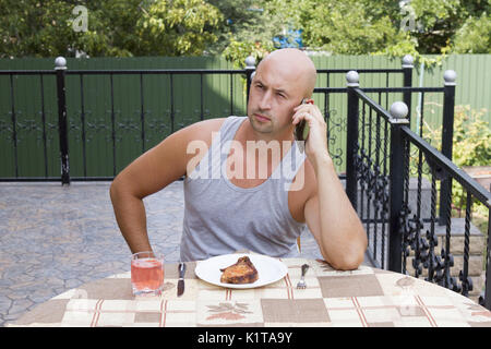 Athletic man is having breakfast on the summer terrace - Stock Photo