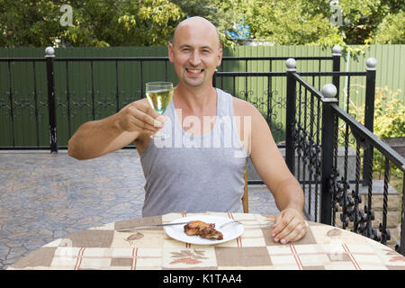 Athletic man is having breakfast on the summer terrace - Stock Photo
