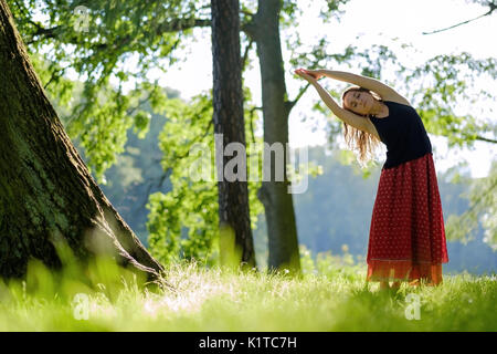 Attractive young female in red skirt is practicing yoga and doing asana in the morning. - Stock Photo