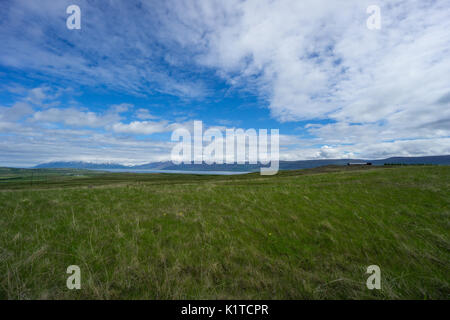 Iceland - Wide green open range with fjord before snowy mountains at blue sky - Stock Photo